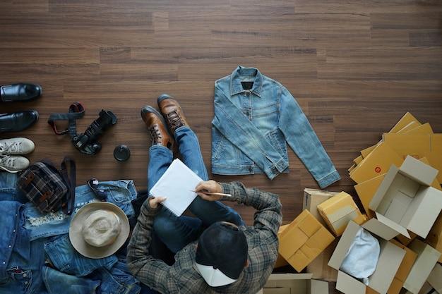 Bovenaanzicht man zittend op een houten vloer en schrijven in notitie boek
