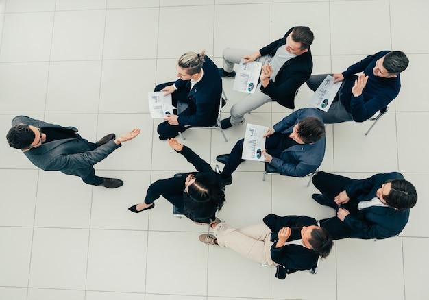 Bovenaanzicht. manager stelt vragen tijdens een zakelijke bijeenkomst. bedrijfsconcept.