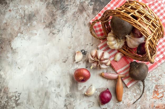 Bovenaanzicht mand met groenten, knoflook, uien en bieten op een lichte foto rijpe dieetkleur salade vrije plaats