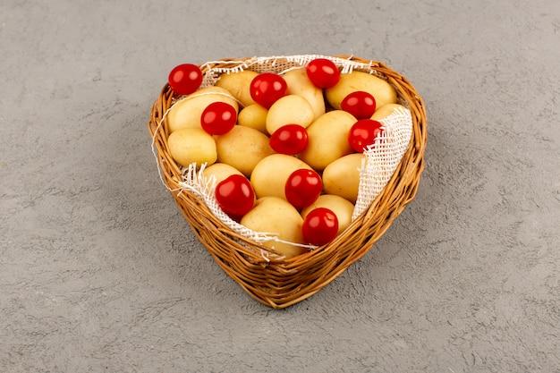 Bovenaanzicht mand met groenten, rode tomaten en aardappelen op de grijze vloer