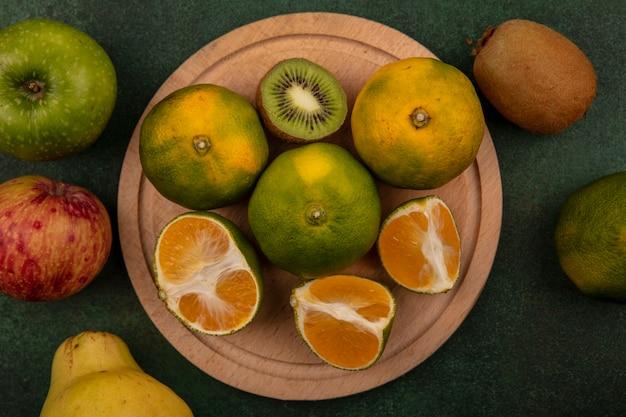 Bovenaanzicht mandarijn plakjes met kiwi plakjes op een stand met appels en peren