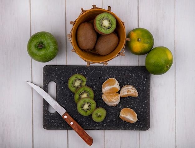 Bovenaanzicht mandarijn plakjes op snijplank met kiwi's in mand en groene mandarijnen en appel