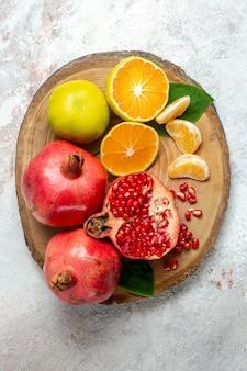 Bovenaanzicht mandarijnen en granaatappels vers zacht fruit op witte achtergrond fruitboom kleur gezondheid vers