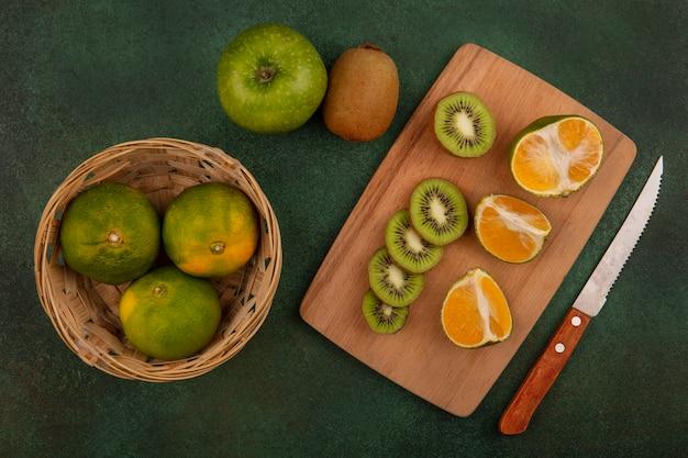 Bovenaanzicht mandarijnen in mand met plakjes kiwi op snijplank met appel