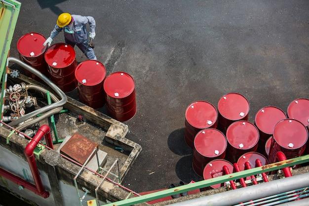 Bovenaanzicht mannelijke werknemer inspectie record drum olie voorraad vaten rood verticaal of chemisch voor in de industrie.