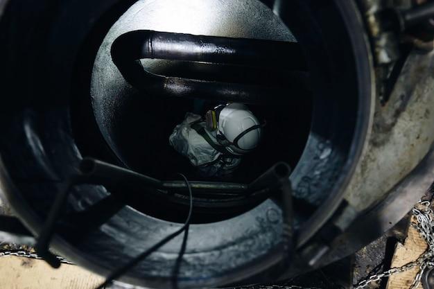 Bovenaanzicht mannelijke werknemer klimt de trap op in de tank, koolstof chemisch vet, veiligheid in besloten ruimten.