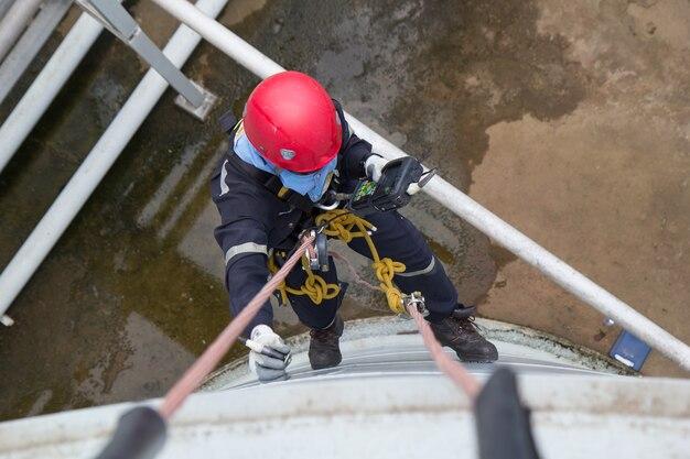 Bovenaanzicht mannelijke werknemer touwtoegang inspectie van dikte opslagtank industrie onder pijpleiding olie