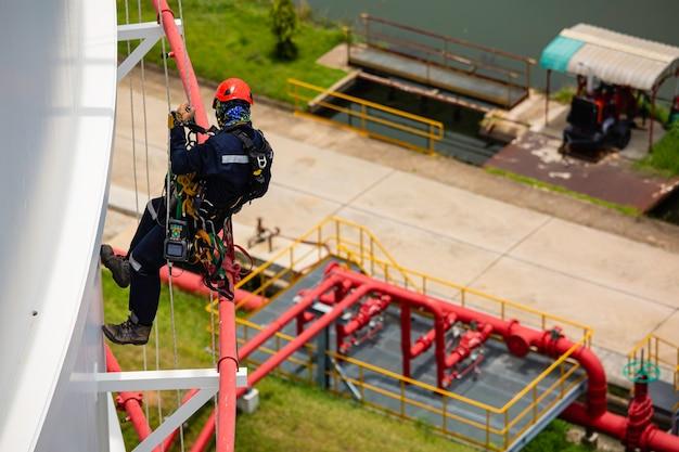 Bovenaanzicht mannelijke werknemers controleren touw naar beneden tank touwtoegang inspectie van dikte schaalplaat opslagtank gasveiligheidswerk op hoogte.