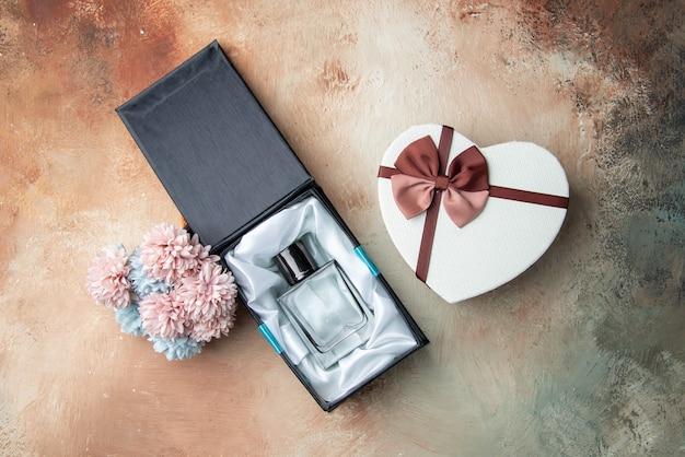 Bovenaanzicht mannen cologne in doos hartvormige doos bloemen op tafel