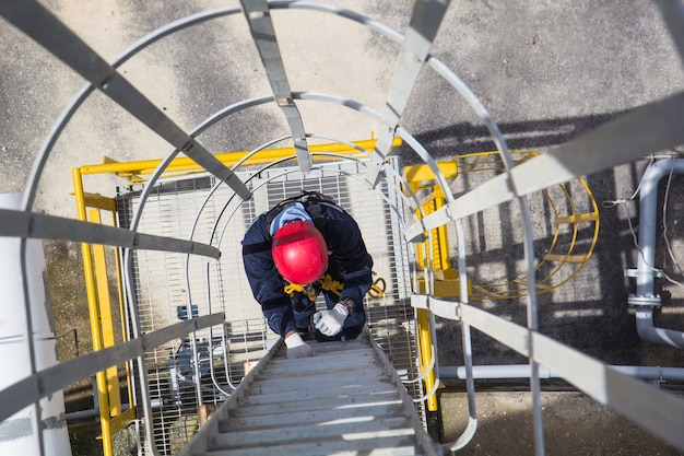 Bovenaanzicht mannetje beklim de koude opslagtank van de ladder