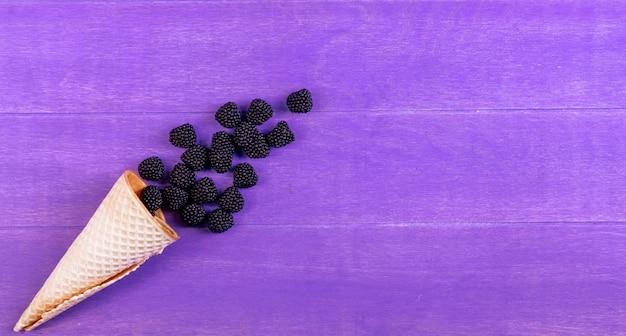 Bovenaanzicht marmelade in de vorm van een braam met een wafel kegel op een paarse achtergrond