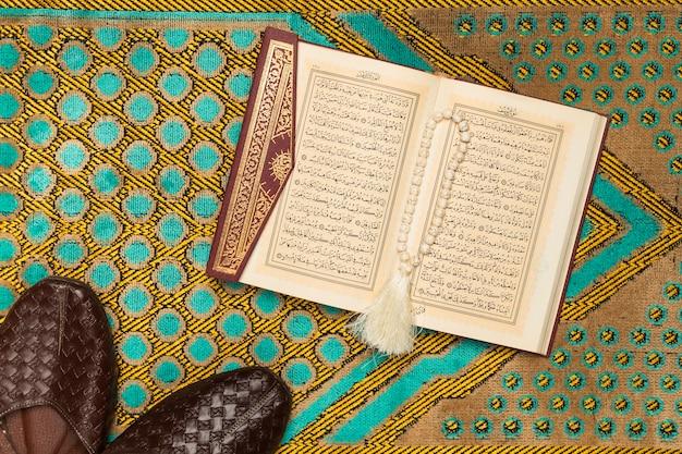 Bovenaanzicht mat met heilige boek en schoenen