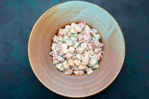 Bovenaanzicht mayonaise salade gesneden groenten binnen plaat op de donkerblauwe achtergrond salade eten maaltijd