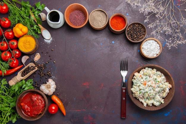 Bovenaanzicht mayyonaise salade met groenten en kruiden op donkere ruimte