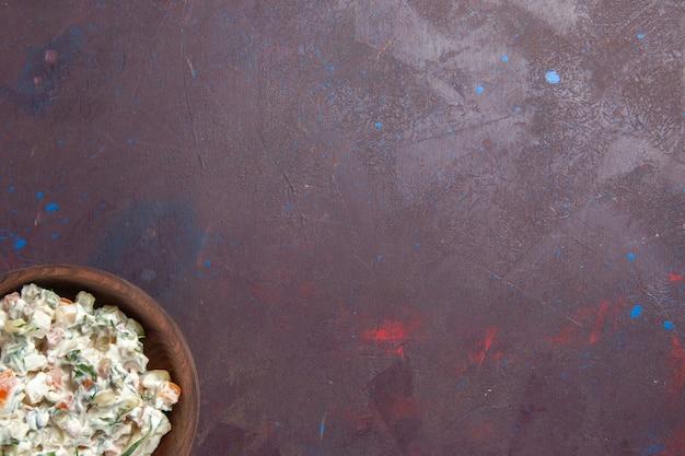 Bovenaanzicht mayyonaise salade met kip in plaat op donker bureau