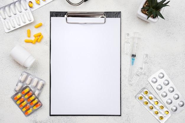 Bovenaanzicht medisch bureau assortiment met leeg klembord