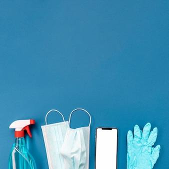 Bovenaanzicht medisch masker en handschoenen met lege telefoon