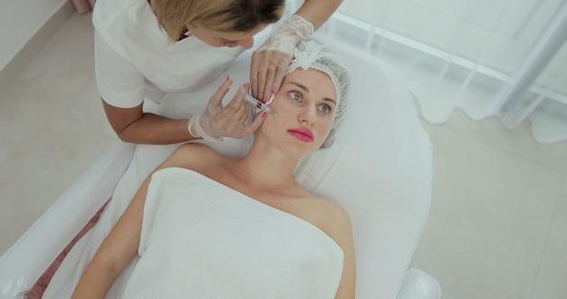 Bovenaanzicht medium close-up shot van bloedplaatjesrijke plasma-injecties in het gezicht. mesotherapie, biorevitalisatie. cosmetologie.