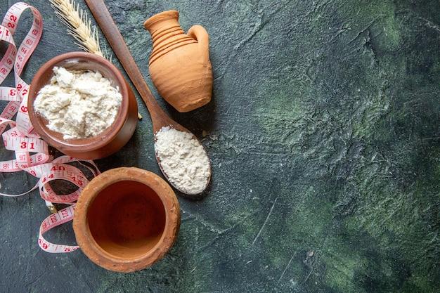 Bovenaanzicht meel in bruine pot met houten lepel op donker bureau