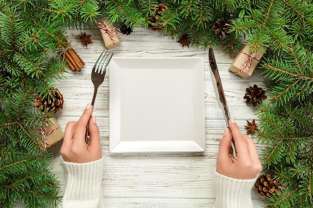 Bovenaanzicht meisje houdt vork en mes in de hand en is klaar om te eten.
