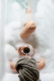 Bovenaanzicht meisje in badkuip met schuim