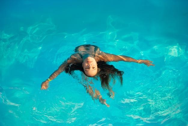 Bovenaanzicht meisje tiener zwemt in het zwembad in warm helder blauw water op zonnige zomeravond tijdens een vakantie in een warm tropisch land. concept herstel en recreatie.