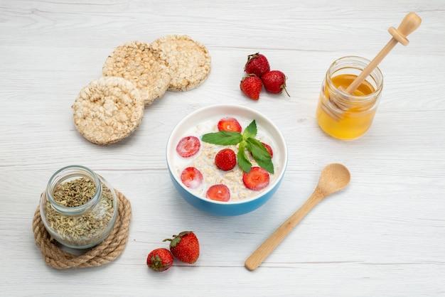 Bovenaanzicht melk met havermout binnen plaat met aardbeien samen met crackers en honing op wit, ontbijtgranen gezondheid