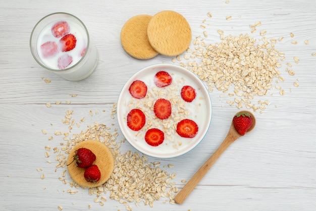 Bovenaanzicht melk met havermout binnen plaat met aardbeien samen met glas melk op wit, zuivel melk ontbijt gezondheid