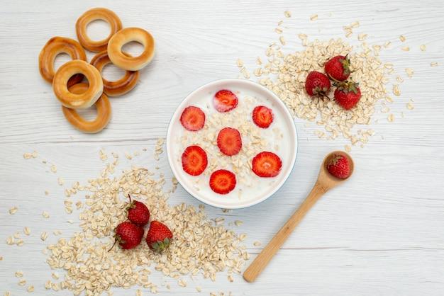 Bovenaanzicht melk met havermout binnen plaat met aardbeien samen met lepel en crackers op wit, zuivel melk ontbijt gezondheid