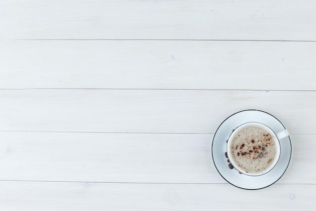 Bovenaanzicht melkachtige koffie in beker op houten achtergrond. horizontaal