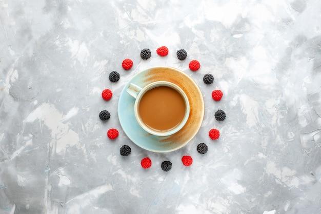 Bovenaanzicht melkkoffie met bessen op de lichte bureaubes drinkt koffiemelk