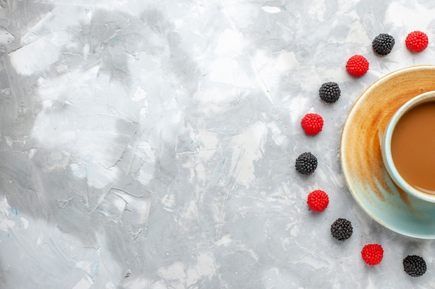 Bovenaanzicht melkkoffie met confituurbessen op de witte achtergrond drinkt zoete melksuikergoed