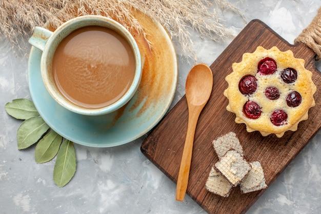 Bovenaanzicht melkkoffie met kersencake op de lichte bureau cake koekje zoete suiker