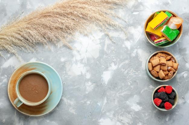 Bovenaanzicht melkkoffie met snoepjes, koekjes en bessen-confitures op de witte achtergrond drink snoep zoete suiker