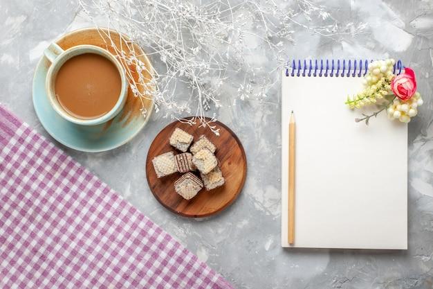 Bovenaanzicht melkkoffie met wafels en blocnote op het lichte koekje van de koffiemelkchocolade