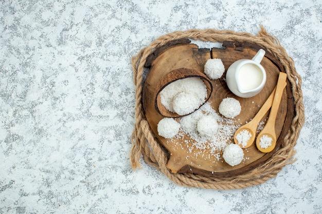 Bovenaanzicht melkkom kokospoeder kom houten lepels kokosballen op een houten bord op grijze achtergrond