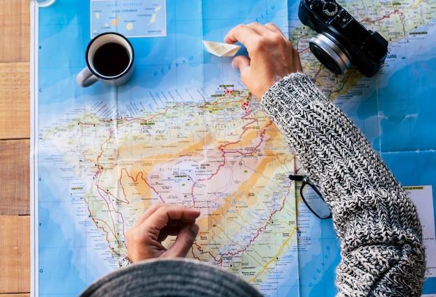 Bovenaanzicht mensen die de volgende bestemming plannen reizen bovenaanzicht met kaart en koffie en fotocamera op tafel - reislust en vakantie-avontuurconcept voor reiziger