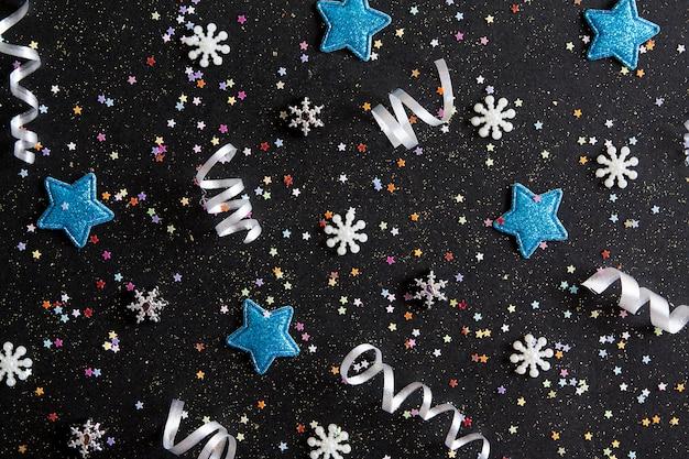 Bovenaanzicht merry christmas zwarte achtergrond versierd met happy new year christmas slingers, sterren, sneeuwvlokken met kopie ruimte. winter vakantie decoratie kaart feestelijk entertainment concept, plat leggen.