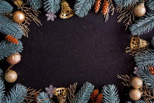 Bovenaanzicht merry christmas zwarte achtergrond versierd met happy new year kerstboom takken en kerstballen met kopie ruimte. winter vakantie kaart decoratie feestelijk leuk concept, plat leggen.