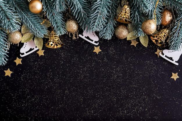 Bovenaanzicht merry christmas zwarte achtergrond versierd met happy new year kerstboom takken, sterren, klokken en kerstballen met kopie ruimte. winter vakantie kaart decoratie feestelijk leuk concept, plat leggen.