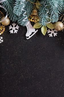 Bovenaanzicht merry christmas zwarte achtergrond versierd met kerstboomtakken, sneeuwvlokken, klokken en kerstballen met kopie ruimte