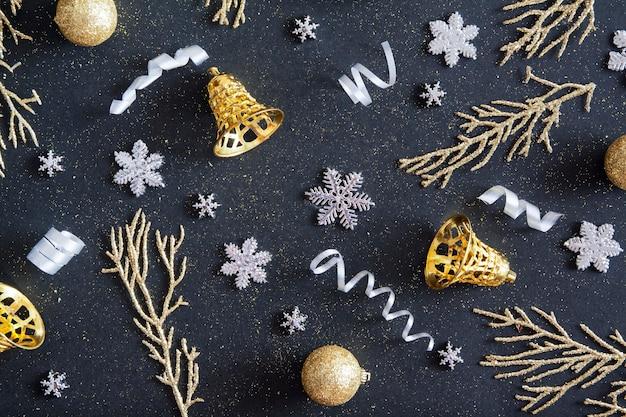 Bovenaanzicht merry christmas zwarte achtergrond versierd met slingers, sneeuwvlokken, gouden klokken. winter vakantie patroon
