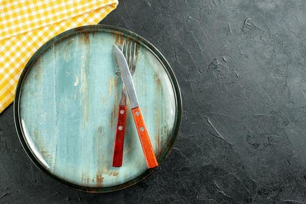 Bovenaanzicht mes en vork op plaat geel wit geruit servet op donkere grond met kopie plaats