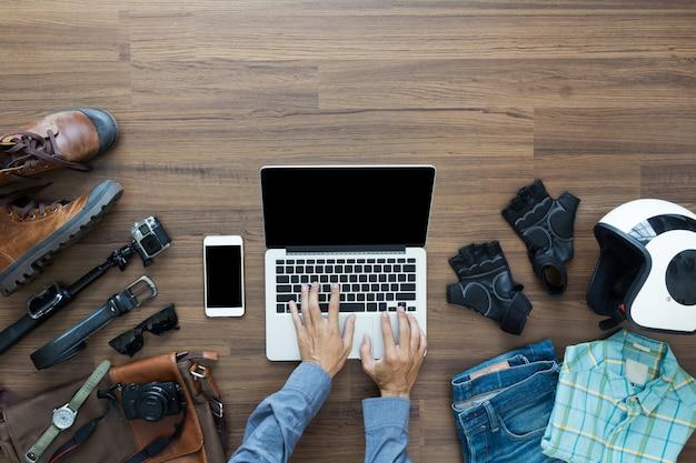 Bovenaanzicht met behulp van laptop met hipster kleding en accessoires op houten