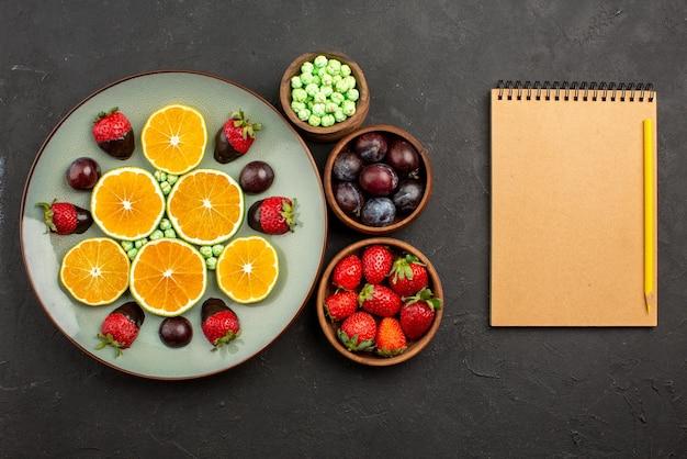 Bovenaanzicht met chocolade bedekte aardbei gehakte sinaasappel met chocolade bedekte aardbei en groene snoepjes en kommen met verschillende soorten fruit, bessen en snoep naast het notitieboekje en het potlood