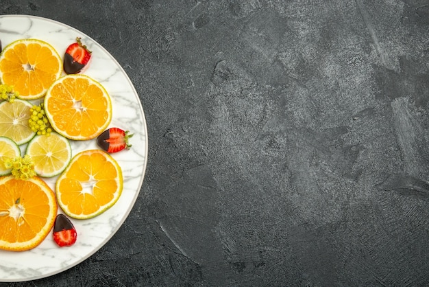 Bovenaanzicht met chocolade bedekte aardbeien, gesneden citroensinaasappel en met chocolade bedekte aardbeien op plaat aan de linkerkant van de donkere tafel