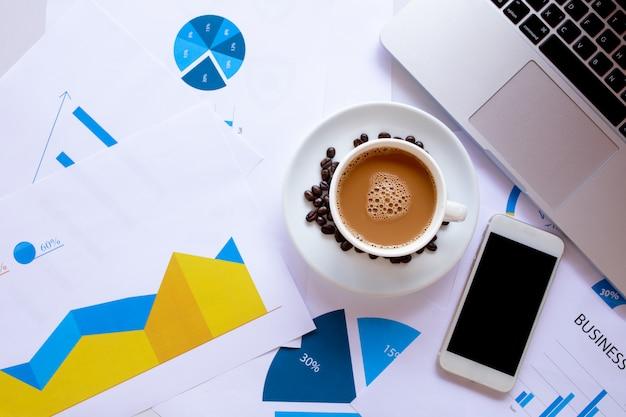 Bovenaanzicht met copyspace voor witte bureau tafel met koffiekopje en koffiebonen, workflows document, computer, smartphone