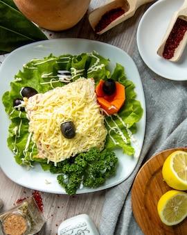 Bovenaanzicht mimosa salade op sla blad met olijven