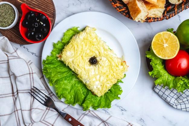 Bovenaanzicht mimosa salade op sla met zwarte olijven citroen en groenten op tafel