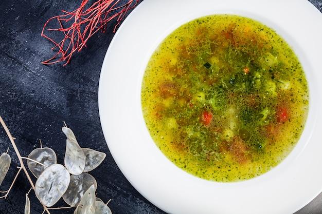 Bovenaanzicht minestrone geserveerd in witte kom op donkere ondergrond
